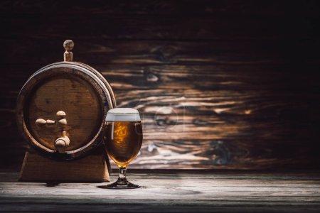 Photo pour Verre de bière et tonneau de bière sur table en bois, concept oktoberfest - image libre de droit