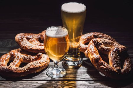 two glasses of beer and yummy pretzels on wooden table, oktoberfest concept