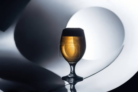glass of beer on reflecting white and black surface, oktoberfest concept