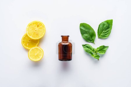 top view of bottle of natural herbal essential oil, lemon pieces and green leaves isolated on white