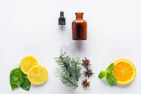 top view of bottle of natural herbal essential oil, dropper, fir, lemon and orange pieces isolated on white