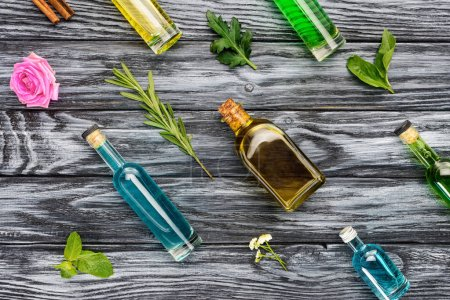 set of colored bottles with natural herbal essential oils on wooden surface