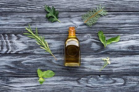 elevated view of bottle of natural herbal essential oil and green leaves on wooden surface