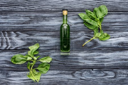 top view of bottle with natural herbal essential oil and green leaves on wooden tabletop