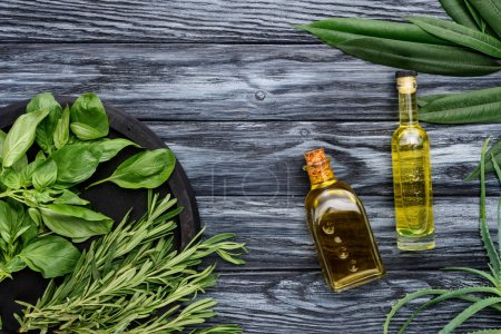 top view of bottles with natural herbal essential oil and green leaves on wooden surface
