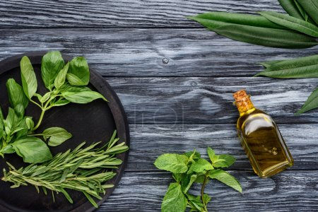 elevated view of bottle with natural herbal essential oil and green leaves on wooden tabletop