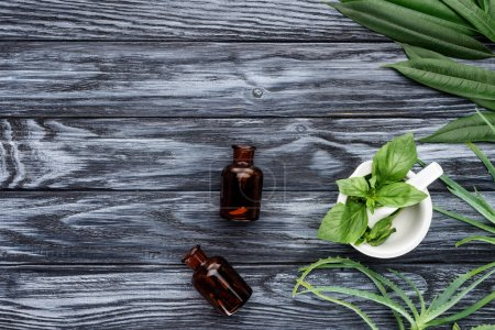 Photo for Top view of two bottles of natural herbal essential oils and green herbs on wooden table - Royalty Free Image