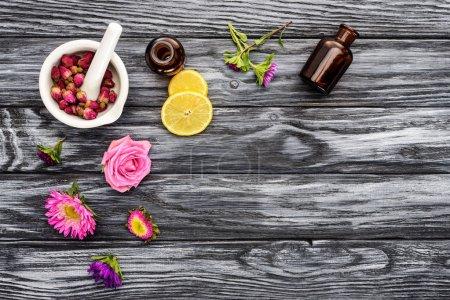 Photo pour Vue de dessus des bouteilles d'huiles essentielles à base de plantes naturelles, de fleurs et d'un pilon de mortier sur une table en bois - image libre de droit