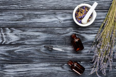 Photo for Top view of bottles of natural herbal essential oils, dropper and dried flowers on wooden table - Royalty Free Image