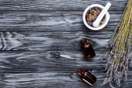 Photo pour Vue de dessus des bouteilles d'huiles essentielles à base de plantes naturelles, compte-gouttes et fleurs séchées sur table en bois - image libre de droit