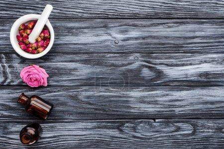 Photo pour Vue de flacons d'huiles essentielles à base de plantes naturelles et des roses sur la surface grise - image libre de droit
