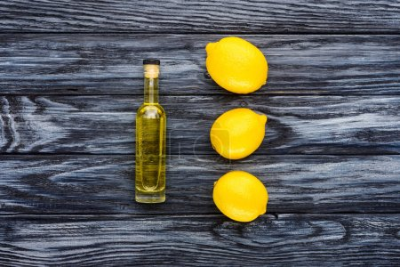 top view of bottle of natural herbal essential oil and three lemons on wooden surface