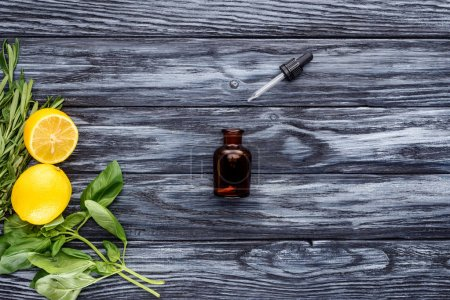 top view of bottle of natural herbal essential oil, dropper and lemons on wooden tabletop