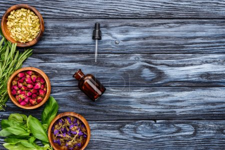 top view of bottle of natural herbal essential oil, dropper and dried flowers on wooden tabletop
