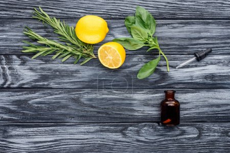 elevated view of bottle of natural herbal essential oil, dropper and lemons on wooden table