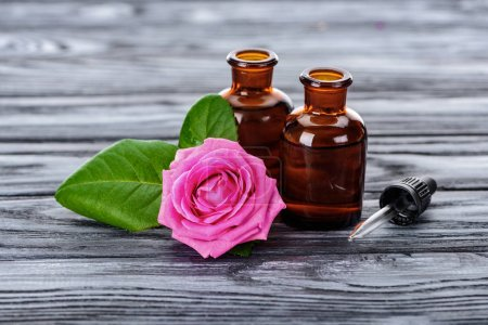 Photo for Bottles of natural herbal essential oils, pipette and pink rose on wooden surface - Royalty Free Image