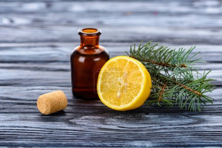 bottle of natural herbal essential oil, fir twigs, lemon and cork on surface