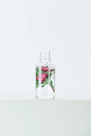 bottle of natural herbal essential oil with flowers on white surface