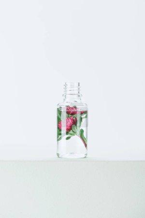 Photo pour Bouteille d'huile naturelle d'essentielles à base de plantes avec des fleurs sur la surface blanche - image libre de droit