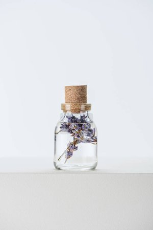 bottle of natural herbal essential oil with violet flowers on white surface