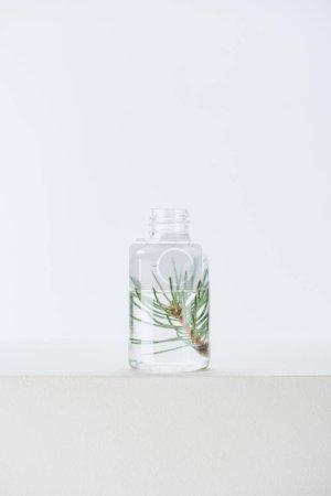 Photo pour Bouteille transparente de naturel à base de plantes huile essentielle avec le rameau de sapin sur la surface blanche - image libre de droit
