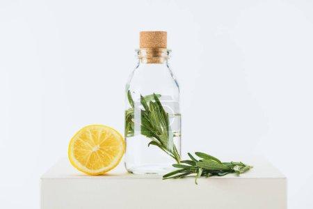 Photo pour Bouteille de naturel huile essentielle à base de plantes avec des rameaux vert et citron sur cube blanc - image libre de droit