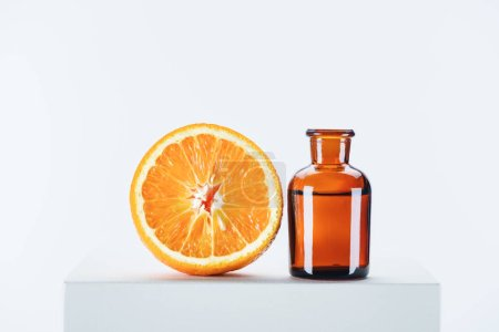 bottle of natural herbal essential oil and cut orange on white cube