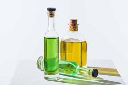 Photo pour Bouteilles d'huiles essentielles naturelles de plantes vertes et jaunes sur cube blanc - image libre de droit