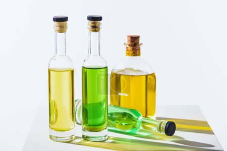 bottles of natural herbal essential green and yellow oils with corks on white surface