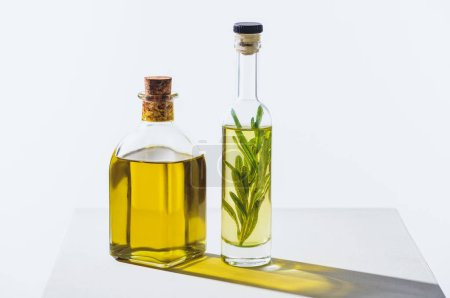 two bottles of natural herbal essential yellow oils on white cube