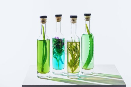 four bottles of natural herbal essential colored oils on white cube