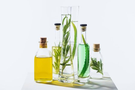 transparent bottles of natural aromatic essential green and yellow oils on white cube