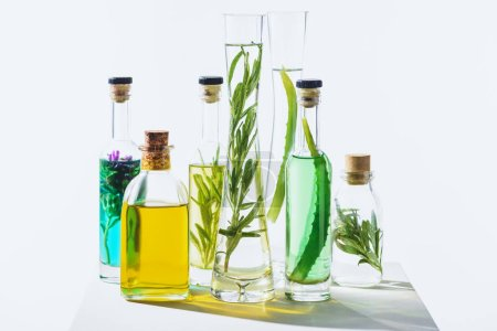 bottles of organic aromatic essential green and yellow oils on white cube