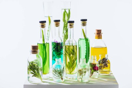 Photo for Different glass bottles of natural herbal essential colored oils on white cube - Royalty Free Image