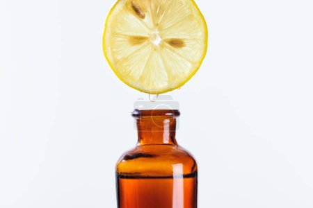 aromatic juice of lemon piece dripping into bottle of natural herbal essential oil isolated on white