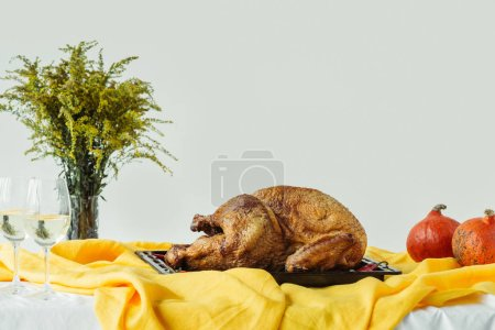 close up view of cooked festive turkey on baking pan, glasses of wine and pumpkins on surface with tablecloth on grey background, thanksgiving holiday concept