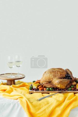 Nahaufnahme der festlichen Dankbarkeitstafel mit Weingläsern, gebratenem Truthahn und Gemüse auf Tischplatte mit Tischdecke