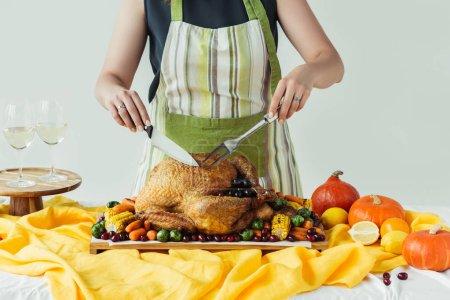Photo pour Vue partielle de la femme en tablier coupe dinde rôtie pour Thanksgiving dîner de vacances sur fond gris - image libre de droit