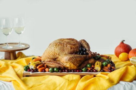 close up view of festive thanksgiving dinner table set with glasses of wine, roasted turkey and vegetables on tabletop with tablecloth
