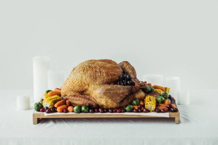 close up view of arranged candles, festive turkey with roasted vegetables for holiday dinner on tabletop, thanksgiving holiday concept