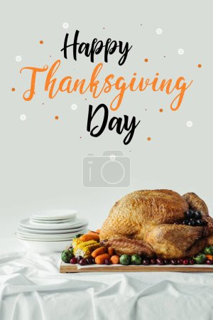 close up view of roasted turkey, cutlery and happy thanksgiving day lettering on grey background