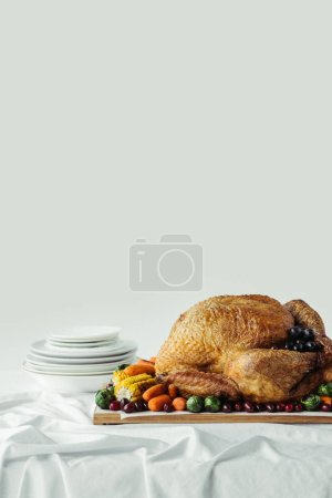 close up view of holiday dinner table set with roasted turkey and vegetables on grey background, thanksgiving holiday concept