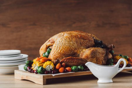 close up view of roasted turkey with vegetables, sauce and cutlery on wooden surface, thanksgiving holiday concept