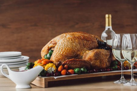 close up view of traditional roasted turkey, vegetables, sauce and glasses of wine for thanksgiving dinner