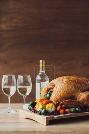close up view of traditional roasted turkey, vegetables and glasses of wine for thanksgiving dinner on wooden tabletop