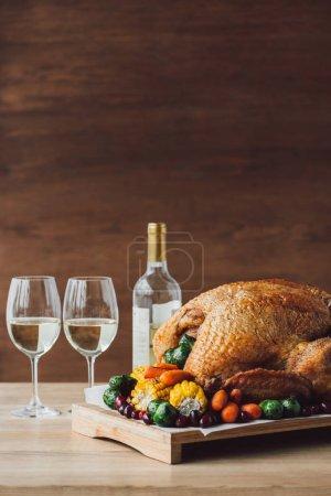 vista de cerca del pavo asado tradicional, verduras y copas de vino para la cena de acción de gracias en la mesa de madera