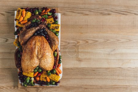 Photo for Top view of roasted turkey and vegetables for thanksgiving traditional dinner on wooden tabletop - Royalty Free Image