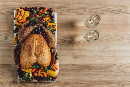 Photo for Top view of roasted turkey, vegetables and glasses of wine for thanksgiving traditional dinner on wooden tabletop - Royalty Free Image