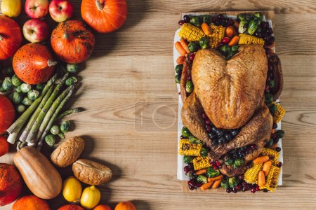 top view of roasted turkey and vegetables for thanksgiving traditional dinner on wooden tabletop
