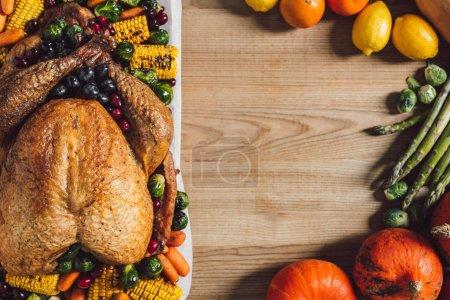 Photo pour Plat posé avec des légumes frais et dinde festive disposée sur une surface en bois, concept de vacances d'action de grâce - image libre de droit